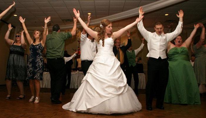 Молодые танцуют в кругу гостей