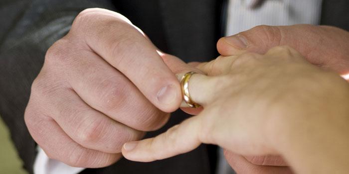 Мужчина одевает девушке кольцо на палец