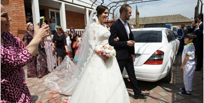 Брат жениха ведет невесту к свадебному кортежу