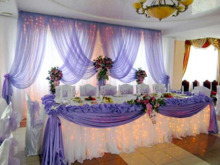 Украшение стола молодоженов композицией из ткани и цветов